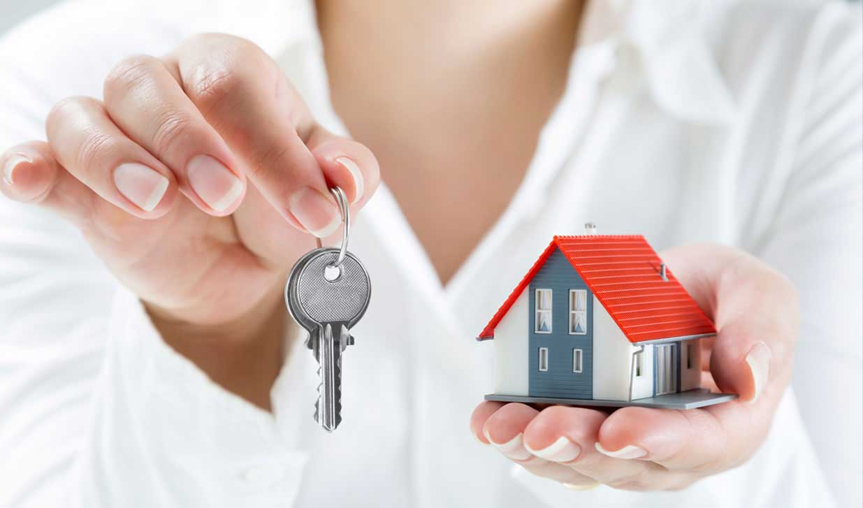 image of woman holding house keys in one hand and rental property in the other.